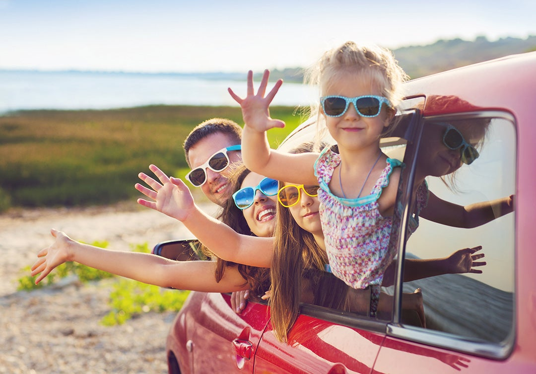Family of 4 wearing sunglasses in red car on vacation