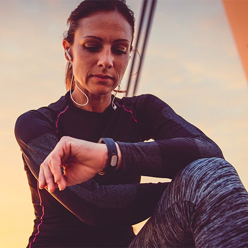 Woman exercising while listening to wireless headphones and checking smart watch